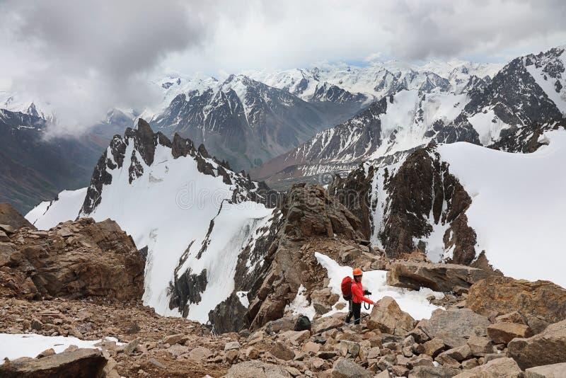 Montanhista fêmea novo em um capacete nas montanhas fotografia de stock