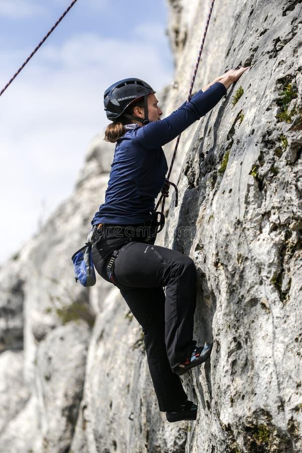 Montanhista fêmea novo que escala uma rota em uma rocha Czestochowska do krakowska de Jura poland imagem de stock royalty free