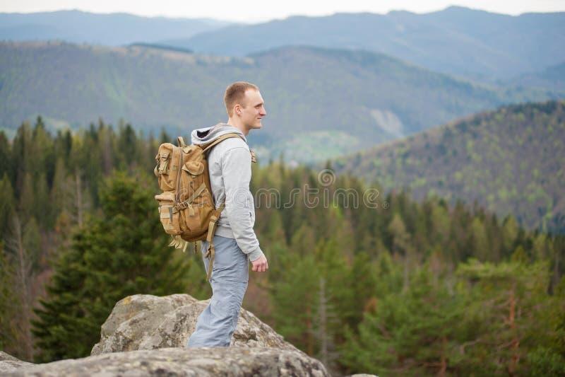 Montanhista masculino com a trouxa marrom no pico da rocha fotografia de stock