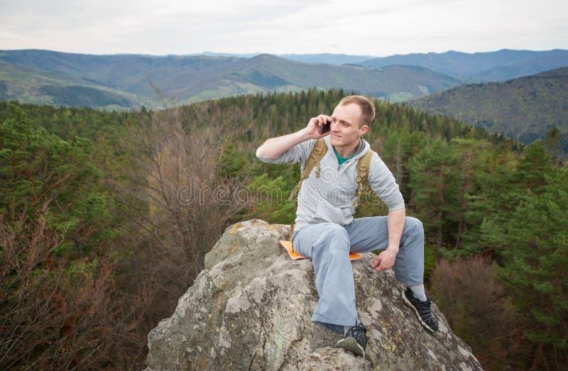 Montanhista masculino com a trouxa marrom no pico da rocha fotos de stock