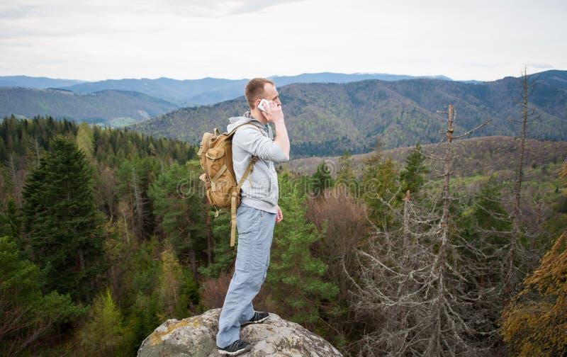 Montanhista masculino com a trouxa marrom no pico da rocha imagens de stock