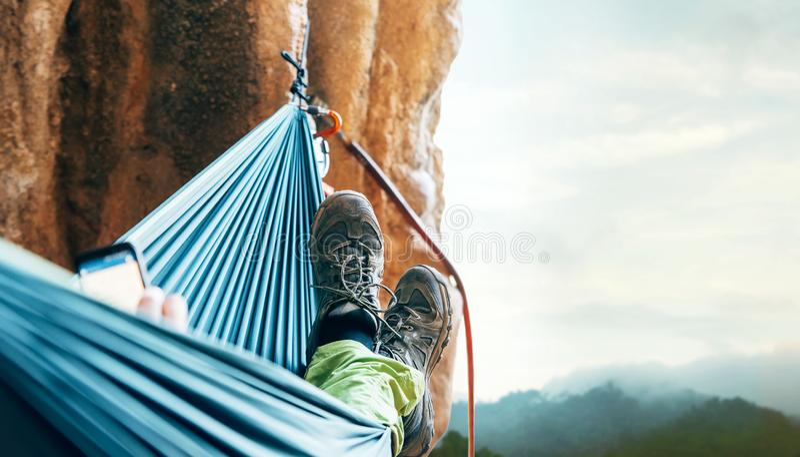 Montanhista que descansa na rede na parede vertical do penhasco fotografia de stock