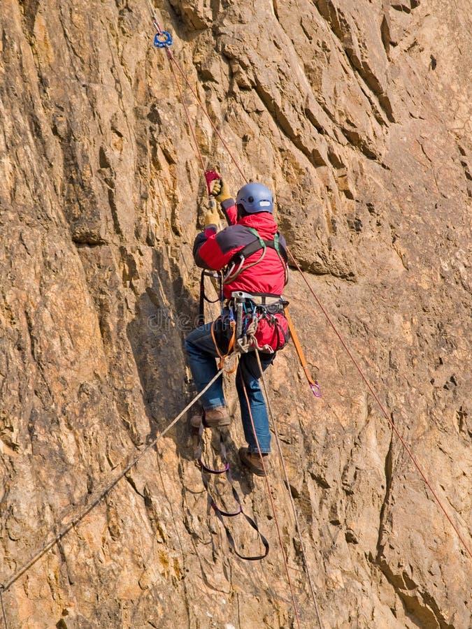 Montanhista que pulula acima da rocha imagens de stock