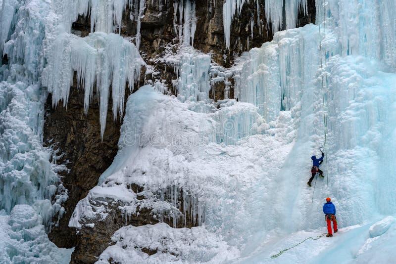 Montanhistas de gelo nas cachoeiras congeladas em Johnston Canyon, Banff fotografia de stock
