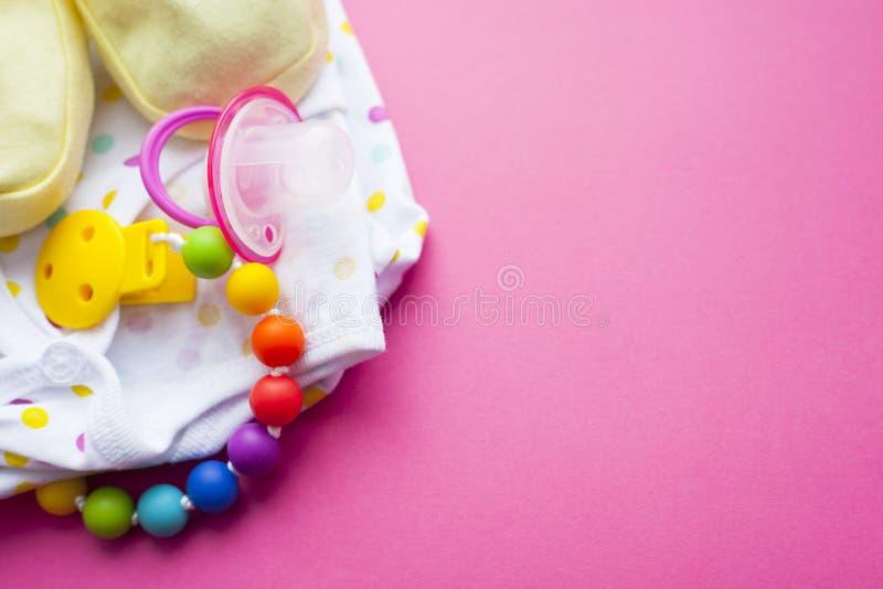 Montantes amarelos do bebê As sapatas e os brinquedos das crianças no fundo cor-de-rosa Recém-nascido imagem de stock