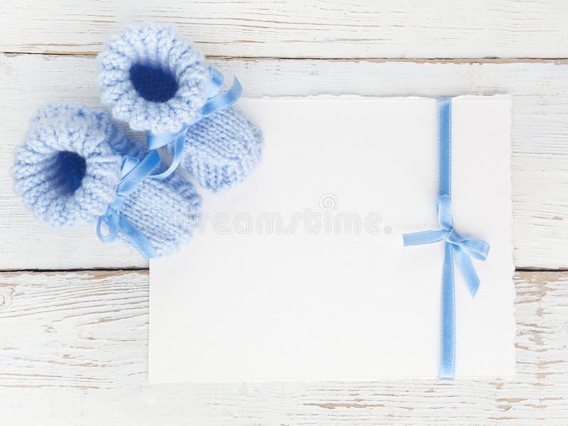 Montantes do bebê com um cartão vazio em um fundo de madeira branco Vista superior Configuração lisa imagens de stock royalty free