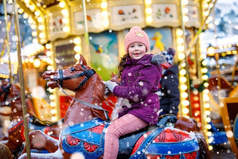 Montar a caballo adorable de la muchacha del niño en un caballo del carrusel en el funfair o el mercado de la Navidad, al aire li fotografía de archivo