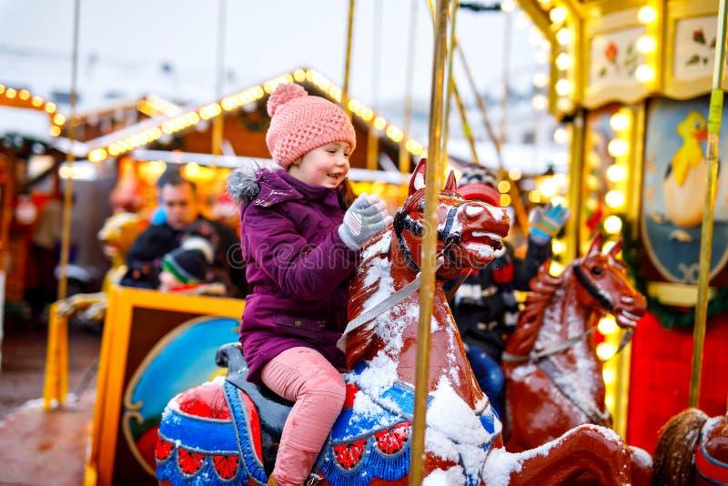 Montar a caballo adorable de la muchacha del niño en un caballo del carrusel en el funfair o el mercado de la Navidad, al aire li fotografía de archivo libre de regalías