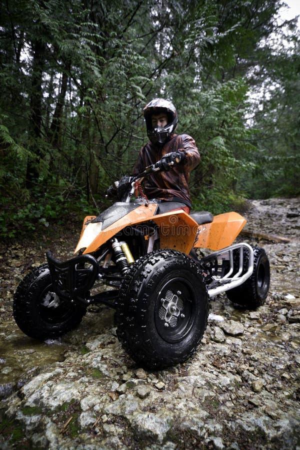 Montar a caballo ATV en montañas fotos de archivo