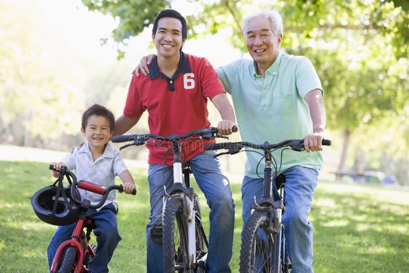 Montar a caballo de abuelo de la bici del hijo y del nieto fotos de archivo libres de regalías