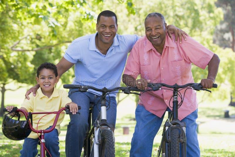 Montar a caballo de abuelo de la bici del nieto y del hijo fotografía de archivo