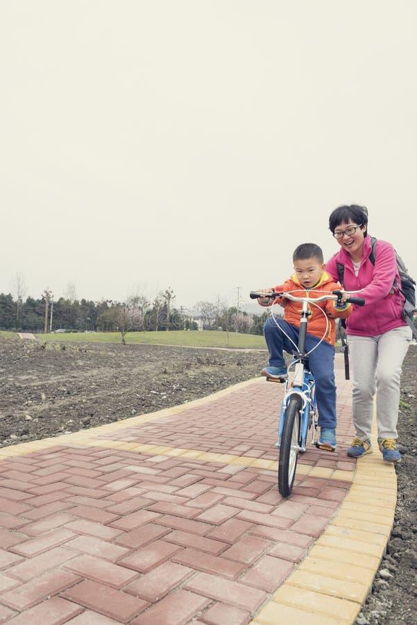 Montar a caballo de enseñanza del hijo de la mamá fotos de archivo libres de regalías
