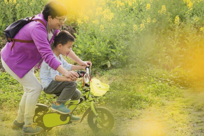 Montar a caballo de enseñanza del hijo de la mamá foto de archivo libre de regalías