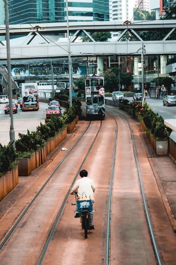 Montar a caballo de la bicicleta en el área para las tranvías del autobús de dos pisos en Hong Kong fotos de archivo libres de regalías