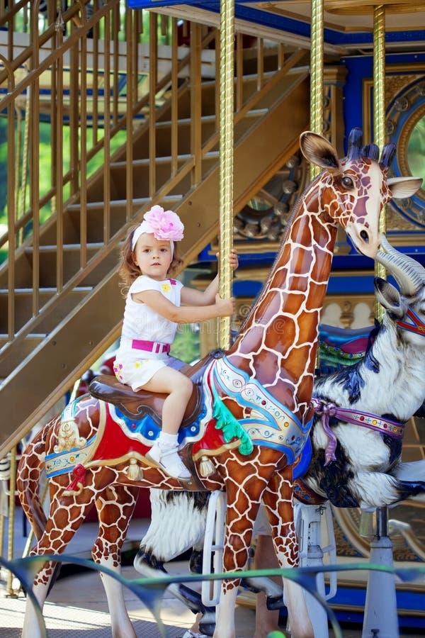 Montar a caballo de la muchacha en un carrusel fotografía de archivo libre de regalías