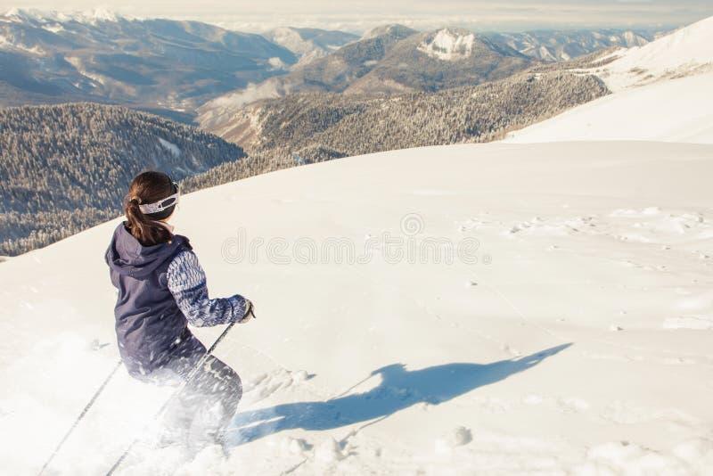 Montar a caballo de la mujer del esquiador por la nieve profunda del polvo imagenes de archivo