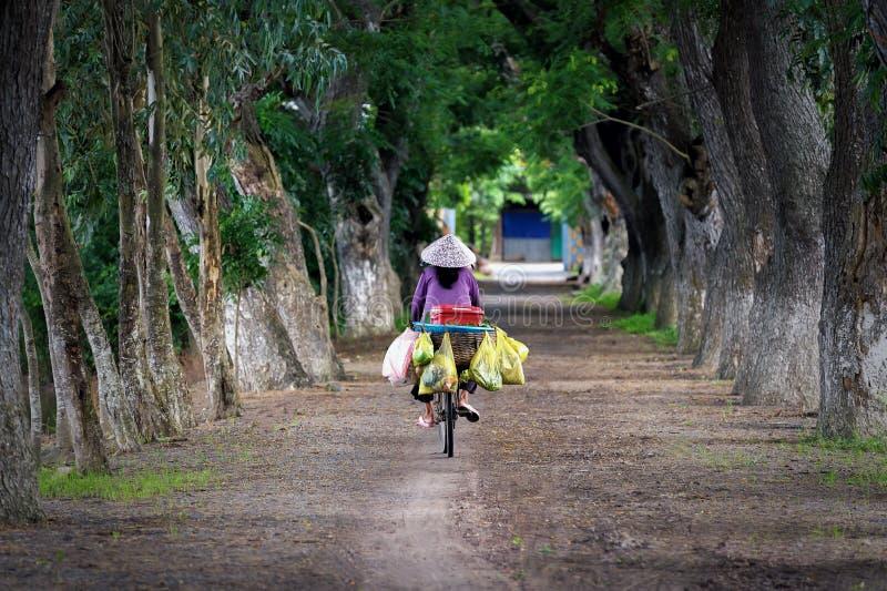 Montar a caballo de la mujer en la bicicleta imagenes de archivo