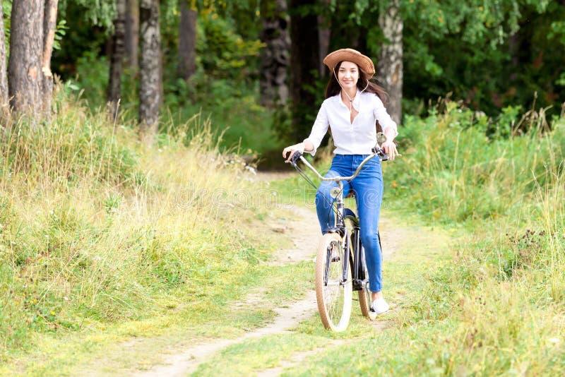 Montar a caballo de la mujer en una bicicleta en un parque del verano imagen de archivo libre de regalías