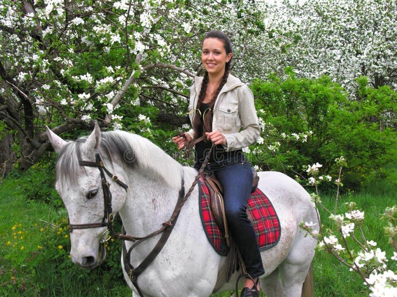 Montar a caballo de la mujer joven en la huerta del resorte fotos de archivo libres de regalías