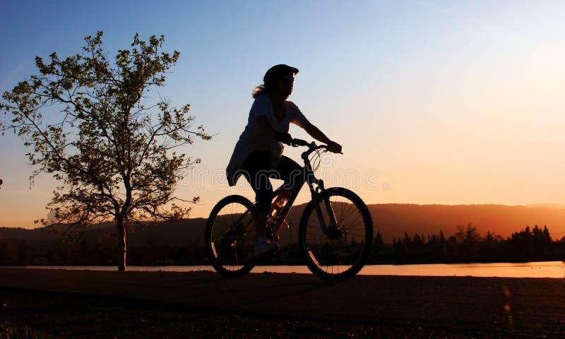 Montar a caballo de la mujer su bici fotografía de archivo libre de regalías