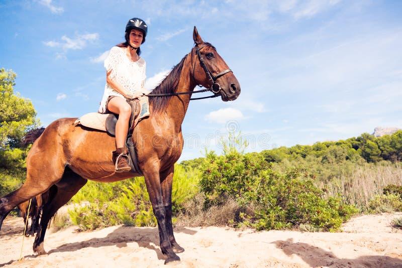 Montar a caballo de lomo de caballo de la mujer joven foto de archivo libre de regalías