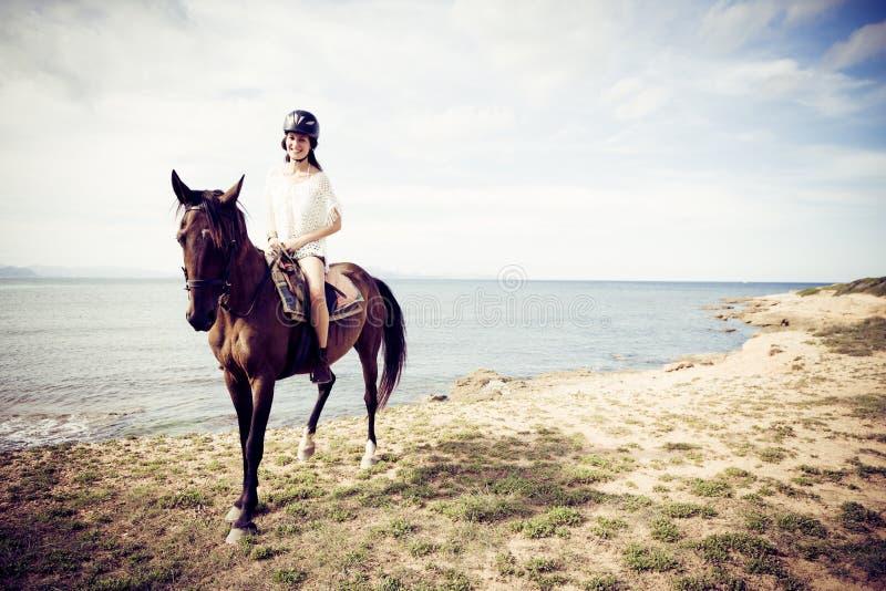 Montar a caballo de lomo de caballo de la mujer joven imágenes de archivo libres de regalías