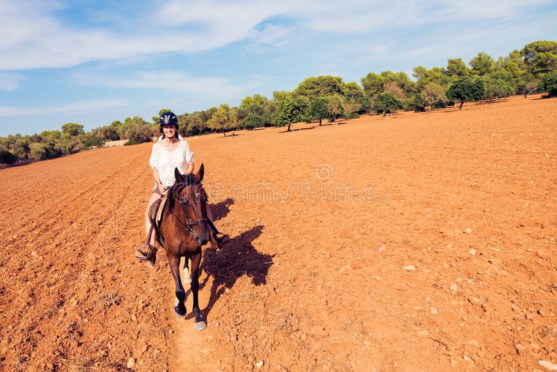 Montar a caballo de lomo de caballo de la mujer joven fotos de archivo