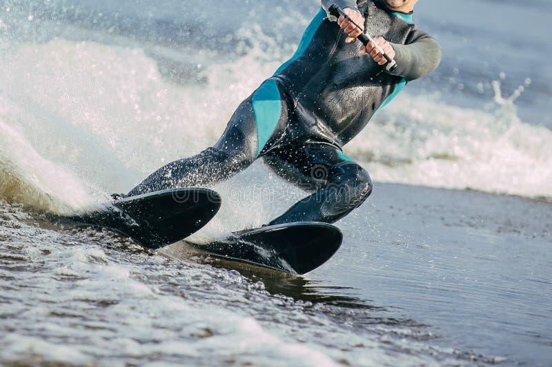 Montar a caballo del hombre en los esquíes acuáticos imagenes de archivo