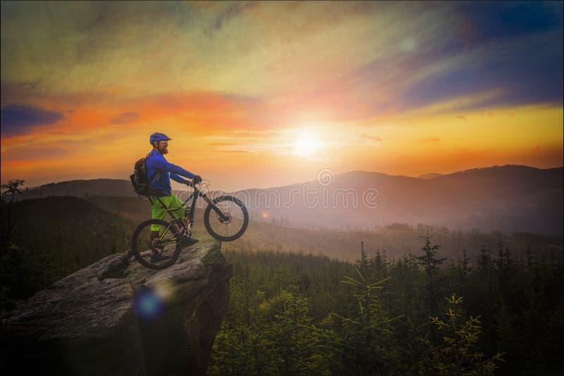 Montar a caballo del motorista de la montaña en la puesta del sol en la bici en las montañas del verano delanteras imagenes de archivo