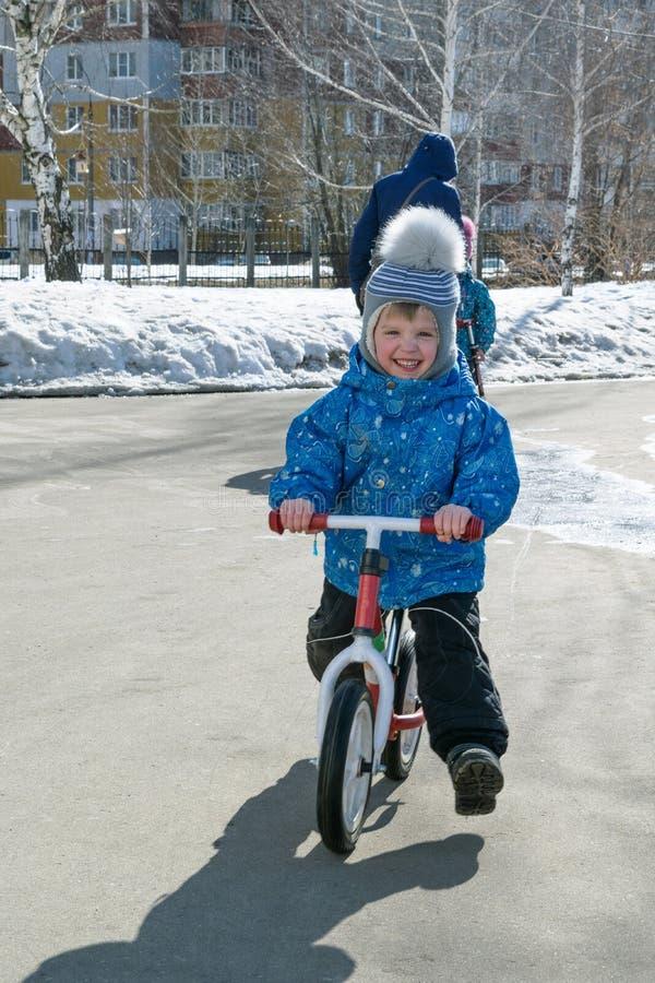Montar a caballo del muchacho en la bici de la balanza El muchacho es feliz fotos de archivo