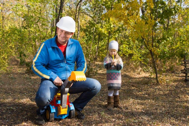 Montar a caballo del padre en su camión del juguete de los childs imagen de archivo