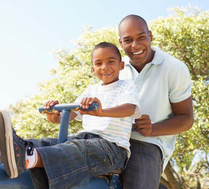 Montar a caballo del padre y del hijo en el balancín en parque imágenes de archivo libres de regalías