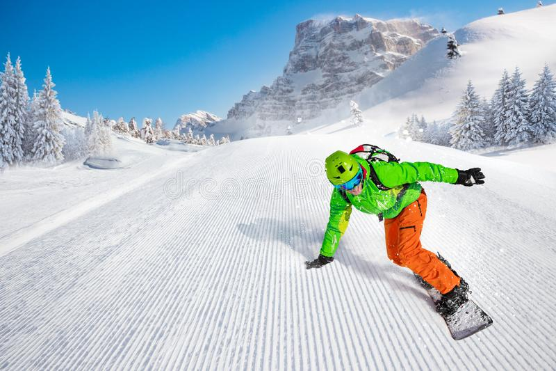 Montar a caballo del snowboarder del hombre en cuesta imagenes de archivo