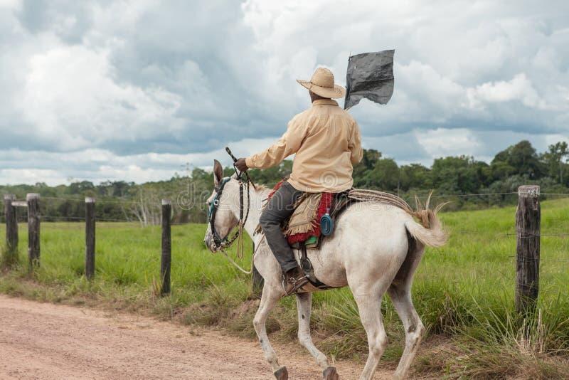 Montar a caballo del vaquero en la granja foto de archivo