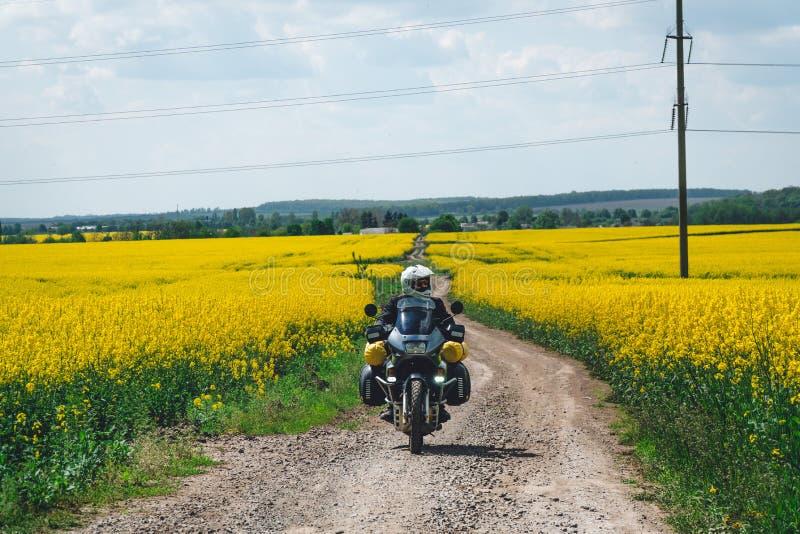Montar a caballo extremo del deporte del hombre que viaja a la motocicleta del enduro en la suciedad campo amarillo hermoso de fl imágenes de archivo libres de regalías
