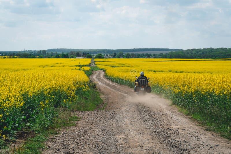 Montar a caballo extremo del deporte del hombre que viaja a la motocicleta del enduro en la suciedad campo amarillo hermoso de fl fotografía de archivo libre de regalías