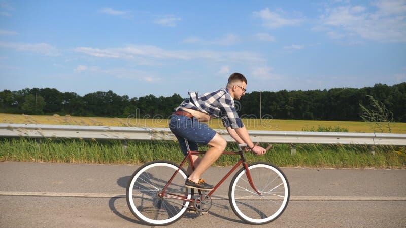 Montar a caballo hermoso joven del hombre en la bicicleta del vintage en la carretera nacional Individuo deportivo que completa u imagenes de archivo