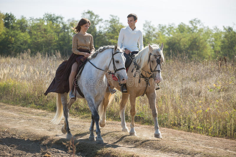 Montar a caballo joven de los pares fotos de archivo libres de regalías