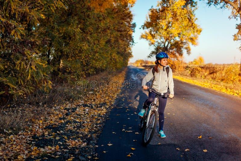 Montar a caballo joven del ciclista en campo del otoño en la puesta del sol Sonrisa feliz de la mujer foto de archivo