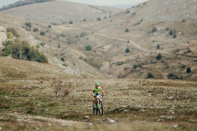 Montar a caballo masculino joven del mountainbiker del ciclista en un valle de la montaña fotografía de archivo libre de regalías