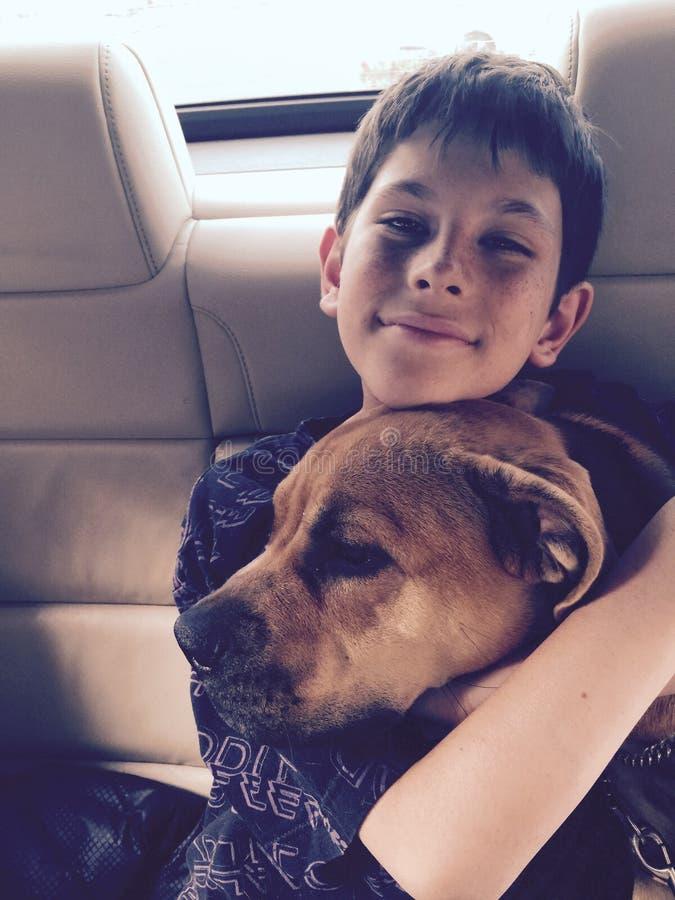 Montar a caballo sonriente del muchacho joven en coche con su perro de perrito imagenes de archivo