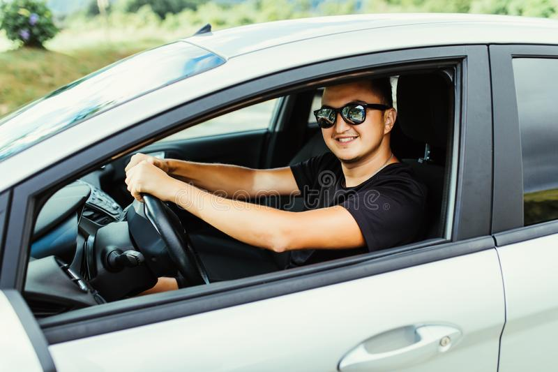Montar su nuevo coche Vista lateral del hombre joven hermoso que conduce su coche y que sonríe al aire libre imagenes de archivo