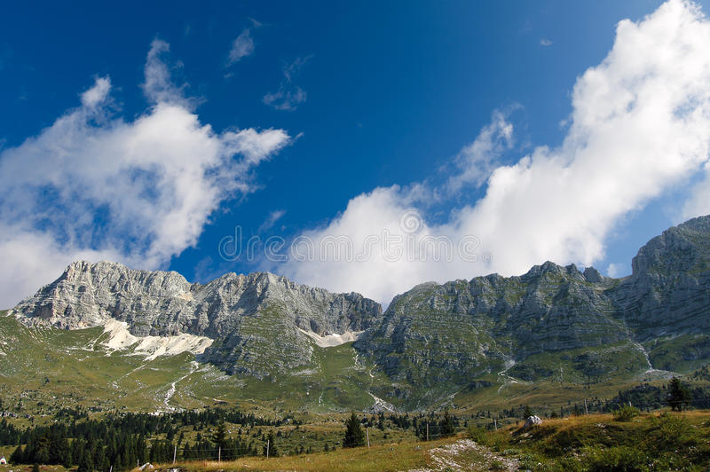 Montasio Plateau and Julian Alps. The high Plateau of Montasio with green pastures in summer and Julian Alps Jof di Montasio. Udine, Friuli Venezia Giulia, Italy stock image