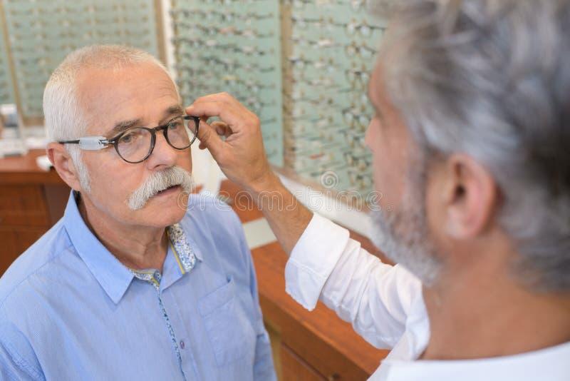 Montature per occhiali di prova dell'uomo senior all'ottico fotografia stock