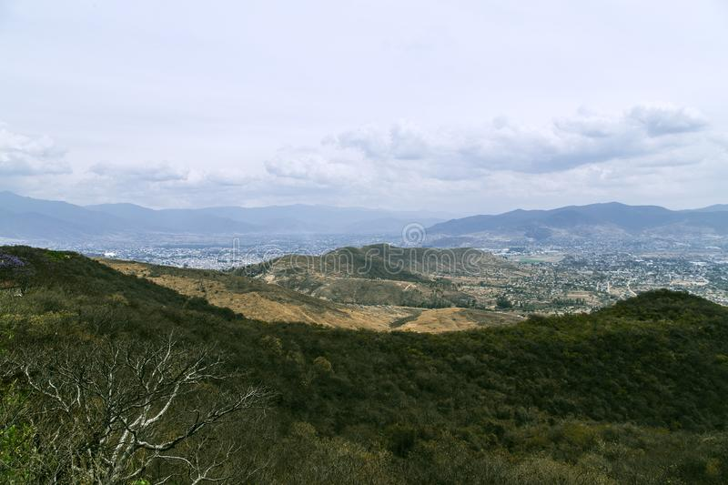 From Monte Alban view over the lower landscapes towards Las Rasas, local village in Oaxaca, Mexico. Monte Alban lights on a higher plateau in the landscape of royalty free stock photos