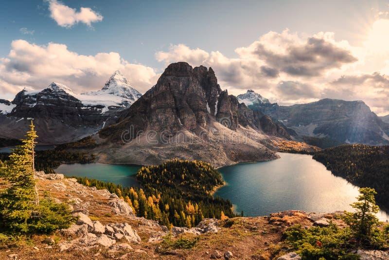 Monte Assiniboine con Sunburst e lago di Cerulean nella foresta di pino autunnale fotografia stock