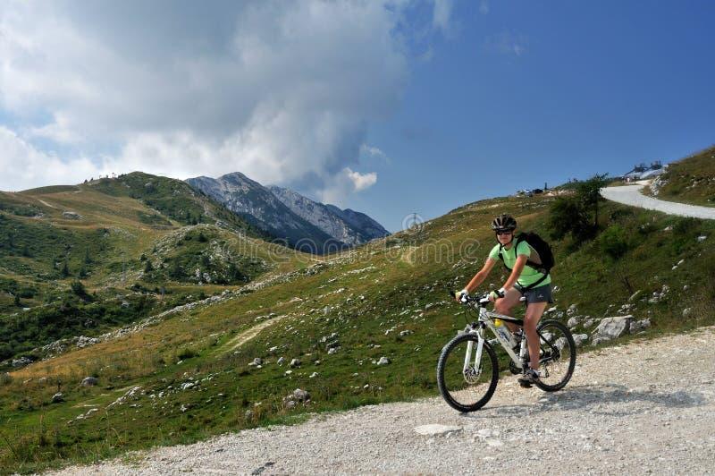 Monte Baldo Biking, Prealpi Gardesane, Italy. Young woman biking down from Mount Baldo peak in Natural park Trentino - Italy royalty free stock image