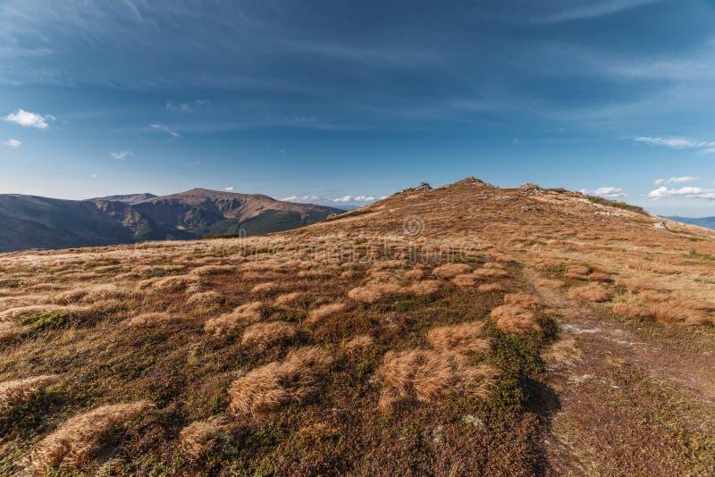 Monte com grama vermelha e rochas com o céu azul profundo imagens de stock