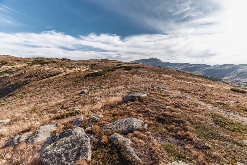 Monte com grama vermelha e rochas com o céu azul profundo fotos de stock royalty free