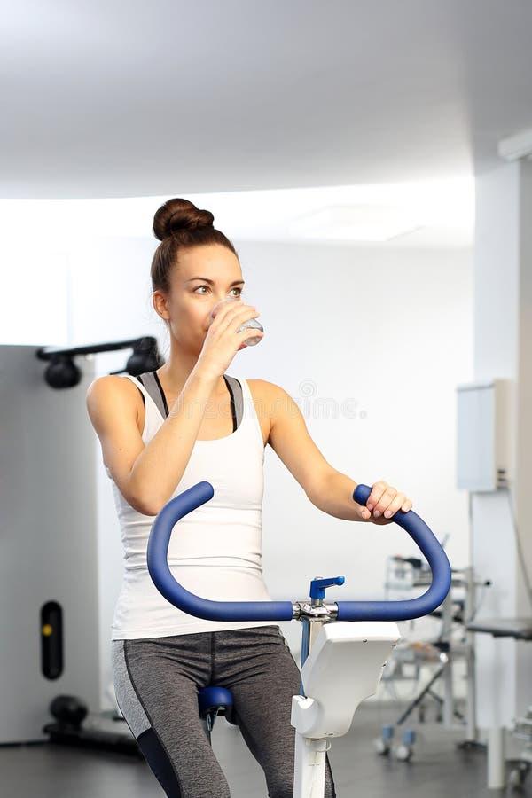 Monte d'une bicyclette stationnaire Rotation, centre de fitness image stock